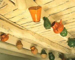 Les pichets de faïence, ici sagement alignés sous les solives du plafond